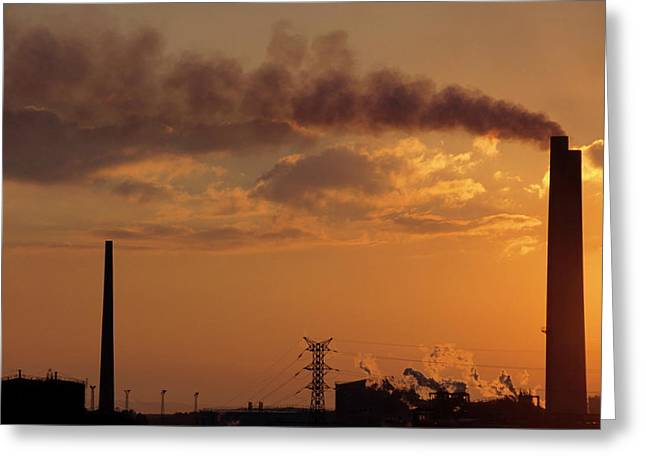 Silhouetted Smoking Chimney At Sunset Greeting Card by Sami Sarkis