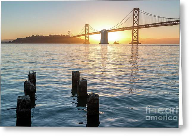 Six Pillars Sticking Out The Water With Bay Bridge In The Backgr Greeting Card