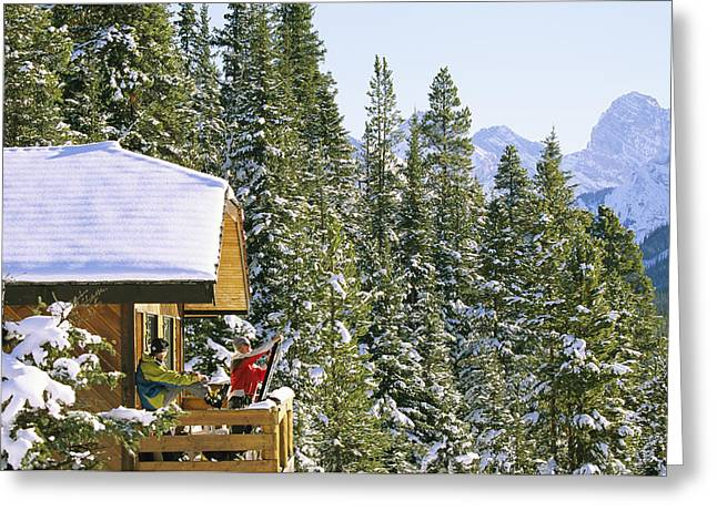 Sportswear Greeting Cards - Skiers On Balcony Of Ski Lodge Prepare Greeting Card by Mark Cosslett