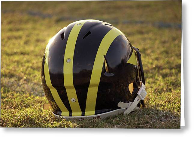 Greeting Card featuring the photograph Striped Wolverine Helmet On The Field At Dawn by Michigan Helmet