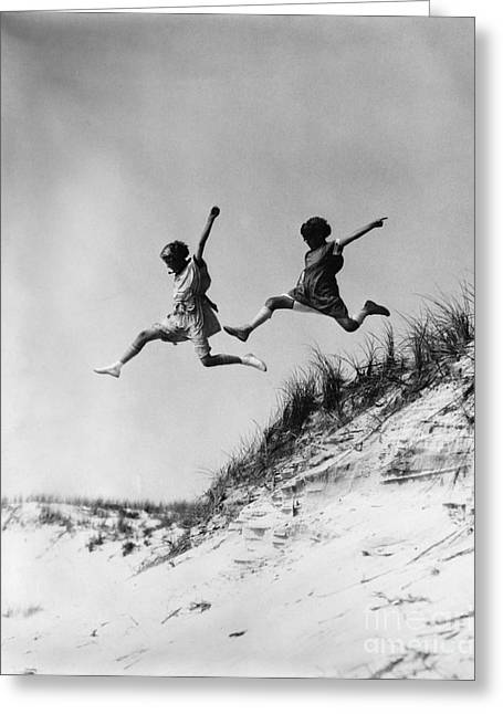 Two Girls Leaping Off Sand Dune Greeting Card by H. Armstrong Roberts/ClassicStock
