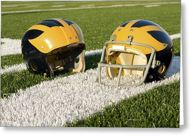 Greeting Card featuring the photograph Wolverine Helmets From Different Eras On The Field by Michigan Helmet
