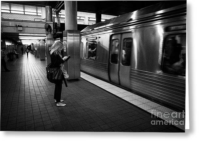 woman checking smartphone as train arrives at septa 2nd street underground subway station Philadelph Greeting Card