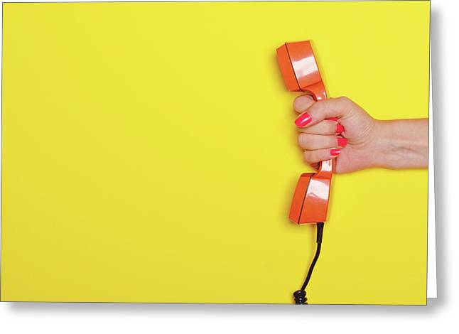 Woman Hand Holding Retro Orange Phone Tube Against Yellow Backgr Greeting Card