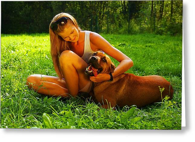 Young Beautiful Woman With Blonde Hair Is Playing With A Mastif Dog In A Backyard With Green Grass Greeting Card by Jozef Klopacka