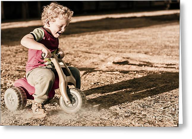 Young Boy Breaking At Fast Pace On Toy Bike Greeting Card