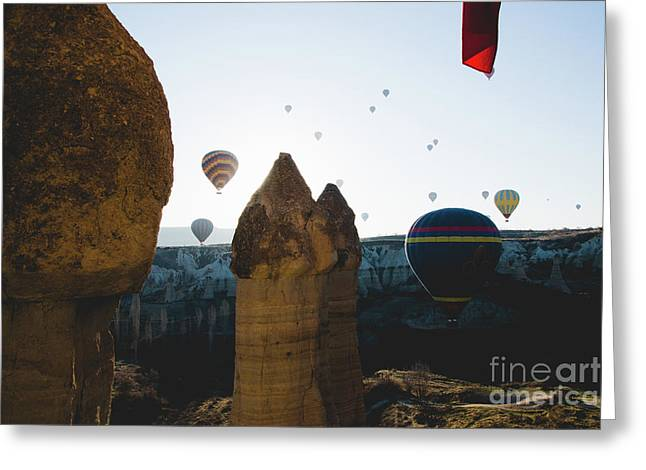 hot air balloons for tourists flying over rock formations at sunrise in the valley of Cappadocia. Greeting Card