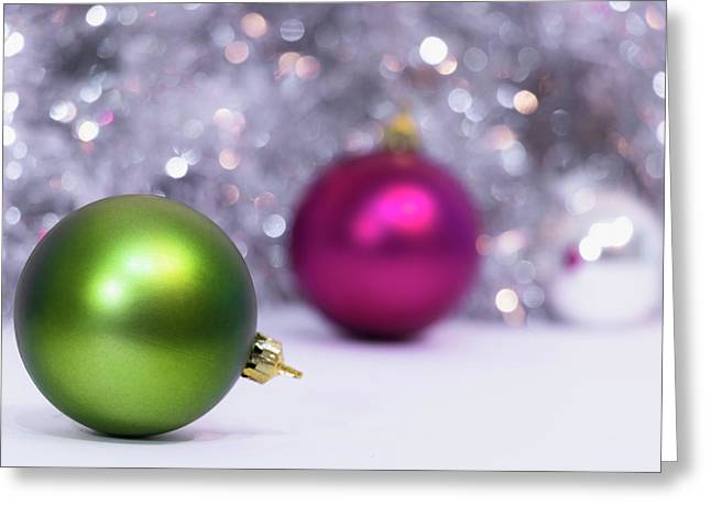 Greeting Card featuring the photograph Green And Fuchsia Christmas Balls And Lights In Background. Wint by Cristina Stefan