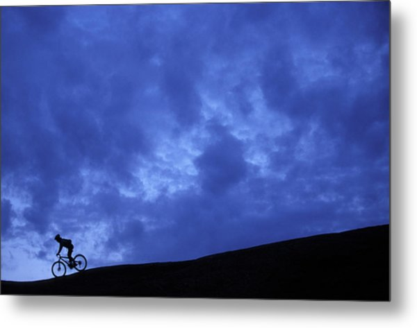 A Silhouette Of A Woman Mountain Biking Metal Print
