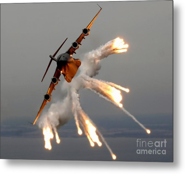 Metal Print featuring the photograph A C-17 Globemaster IIi Releases Flares by Stocktrek Images