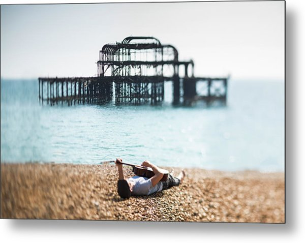 A Man Lying On A Beach With A Guitar Metal Print
