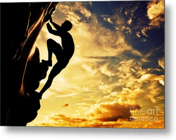 A Silhouette Of Man Free Climbing On Rock Mountain At Sunset Metal Print