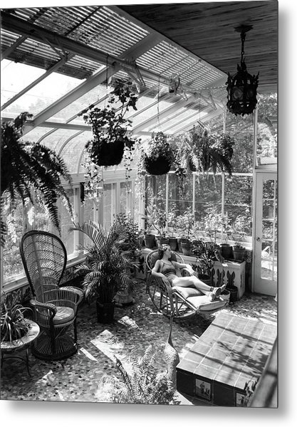 A Woman Resting On A Chair Inside A Greenhouse Metal Print
