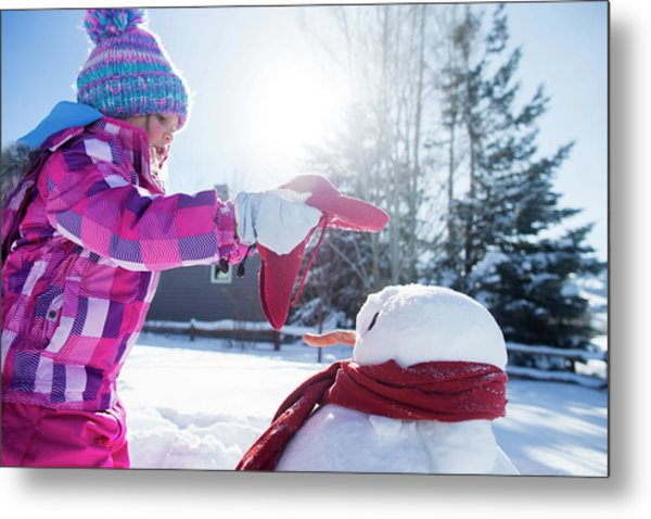 A Young Girl Building A Snowman Metal Print