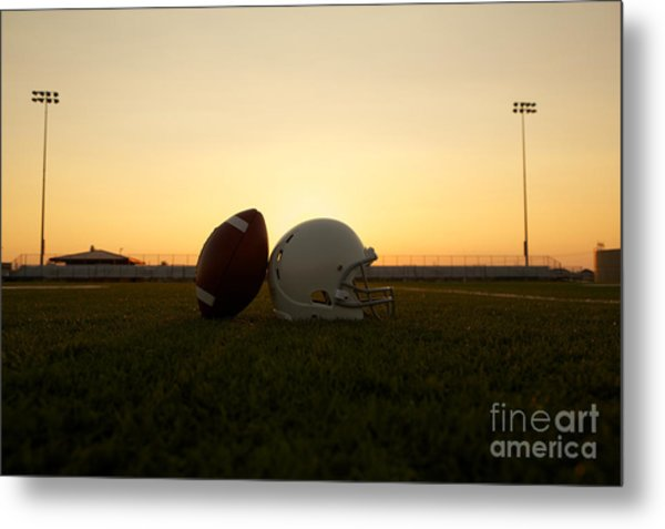 American Football And Helmet On The Field At Sunset Metal Print