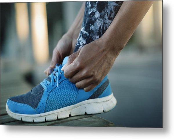 Close-up Of Woman Tying Shoelace On Bench Metal Print by Maskot