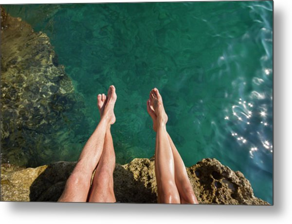 Couples Legs Above Turquoise Ocean Metal Print by Picturegarden