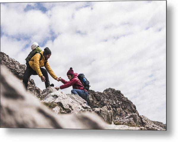Germany, Bavaria, Oberstdorf, Man Helping Woman Climbing Up Rock Metal Print by Westend61