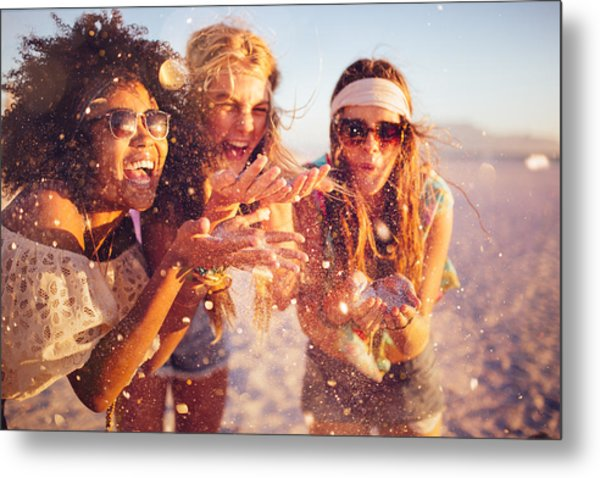 Girls Blowing Confetti From Their Hands On A Beach Metal Print by Wundervisuals