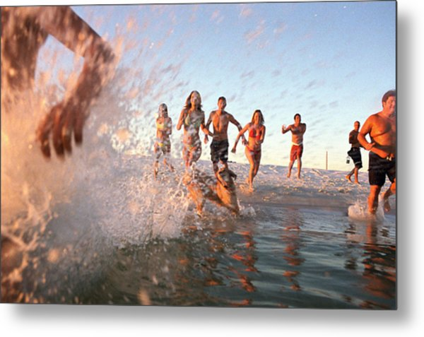 Group Of Young Adults Running Through Water At Ocean's Shore Metal Print by Sean Murphy