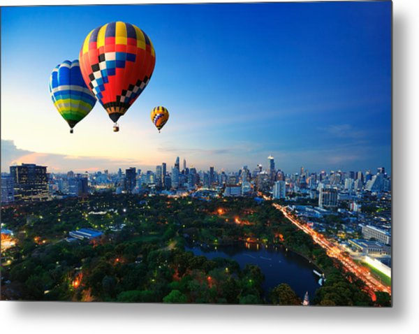 Hot Air Balloons Fly Over Cityscape At Sunset Background Metal Print by Busakorn Pongparnit