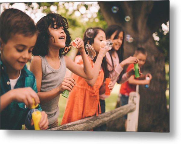 Little Boy Having Fun With Friends In Park Blowing Bubbles Metal Print by Wundervisuals