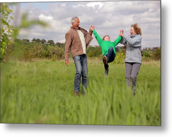 Mature Couple Swinging Grandchild In Metal Print by Bloom Productions