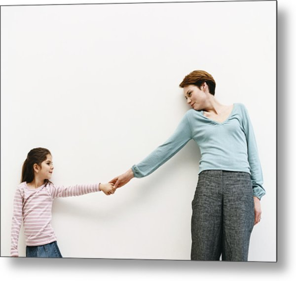 Mother And Her Daughter Stand By A Wall, Reaching Out And Holding Hands Metal Print by Dylan Ellis