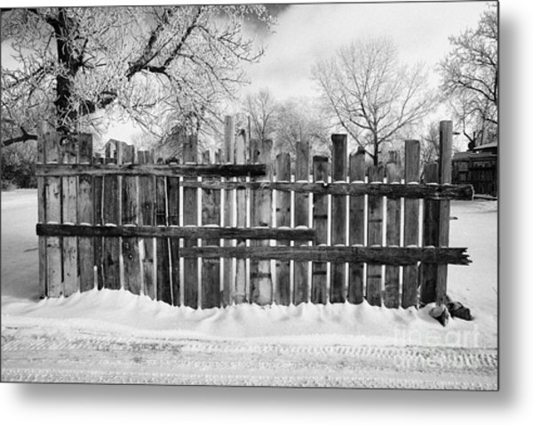old patched up wooden fence using old bits of wood in snow Forget Saskatchewan  Metal Print by Joe Fox