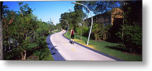 Rear View Of Woman Jogging In A Park Metal Print