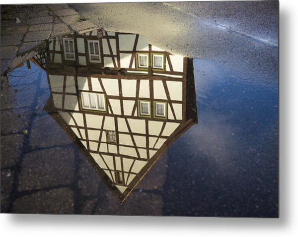Reflection Of A Beautiful Old Half-timbered House In A Puddle Of Water Metal Print