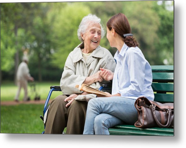 Senior Woman With Caregiver In The Park Metal Print by FredFroese