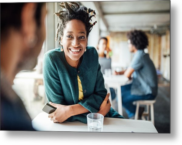 Smiling Businesswoman Sitting With Colleague In Cafeteria Metal Print by Luis Alvarez
