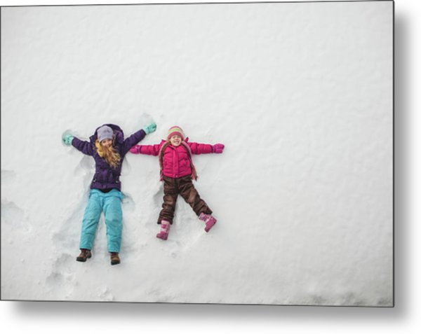 Two Sisters Playing, Making Snow Angels Metal Print by Hugh Whitaker