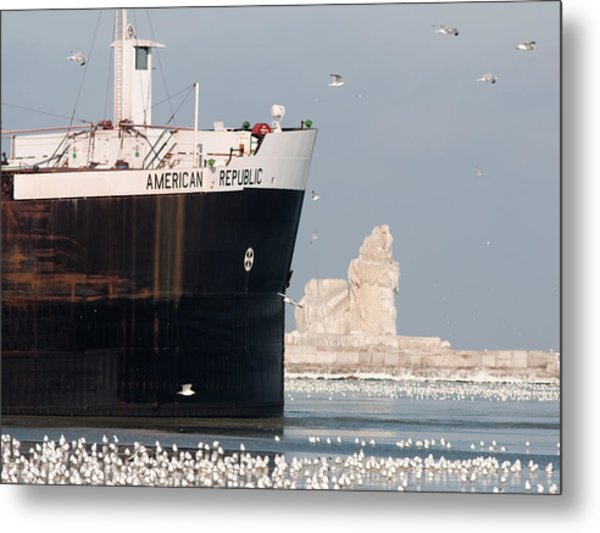 Great Lakes Ship Passing A Frozen Cleveland Lighthouse Metal Print