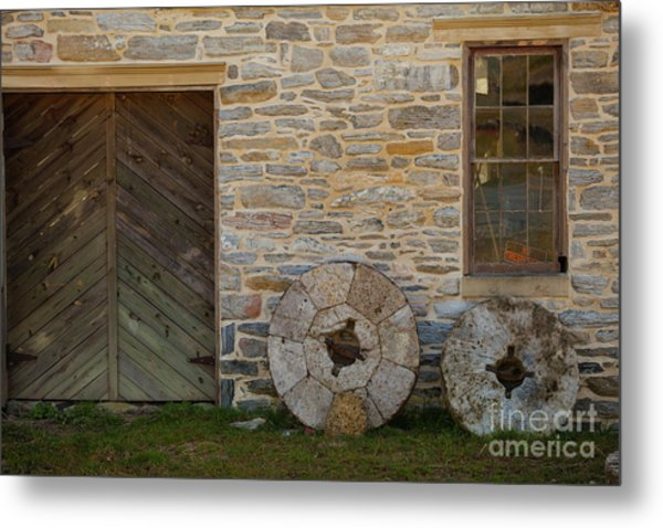 Two Mill Stones Against Building Metal Print