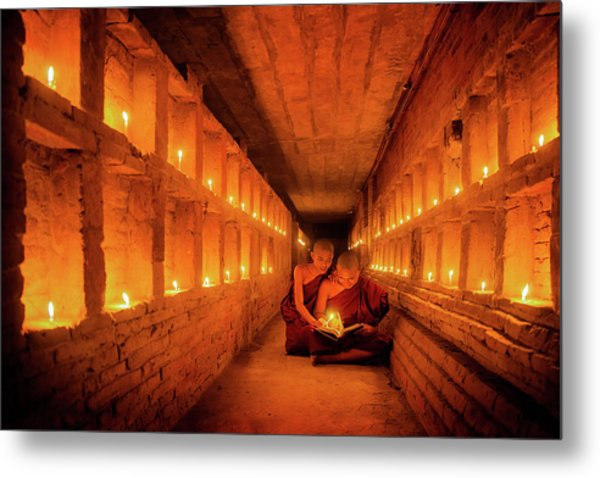 Young Buddhist Monk Are Reading A Book With Light From Candle  Metal Print by Anek Suwannaphoom