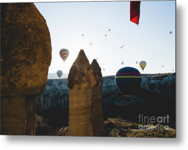 hot air balloons for tourists flying over rock formations at sunrise in the valley of Cappadocia. Metal Print