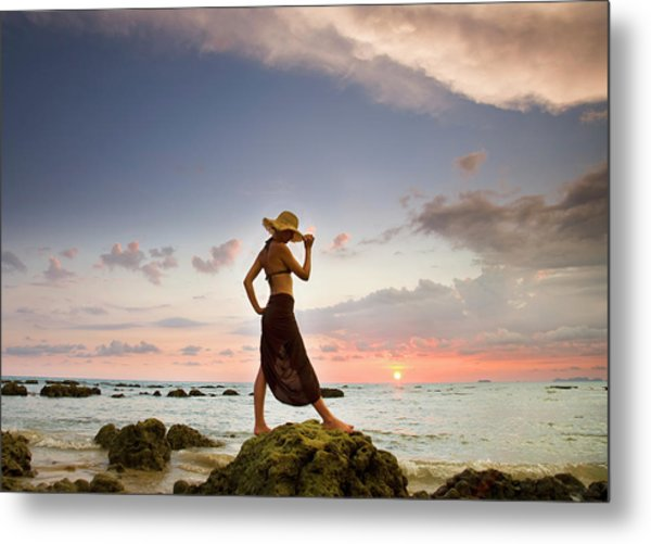 A Woman Wearing A Hat And Sarong Stands Metal Print