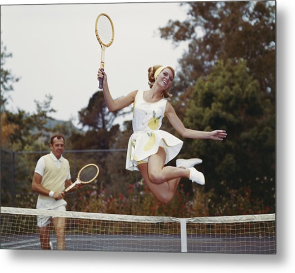 Couple On Tennis Court, Woman Jumping Metal Print by Tom Kelley Archive