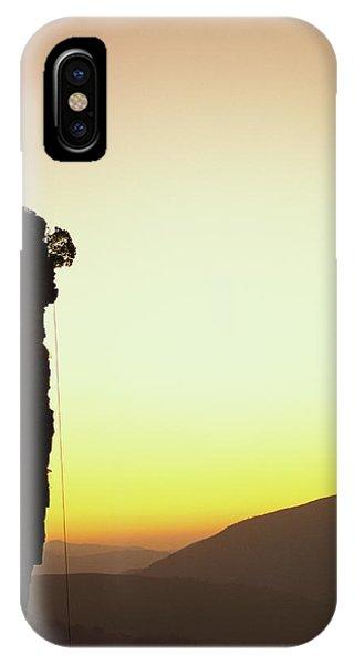 Sunrise iPhone Case - A Climber Stands Atop A Cliff by Bill Hatcher