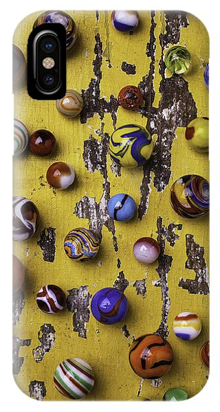 Novelty iPhone Case - Marbles On Yellow Wooden Table by Garry Gay