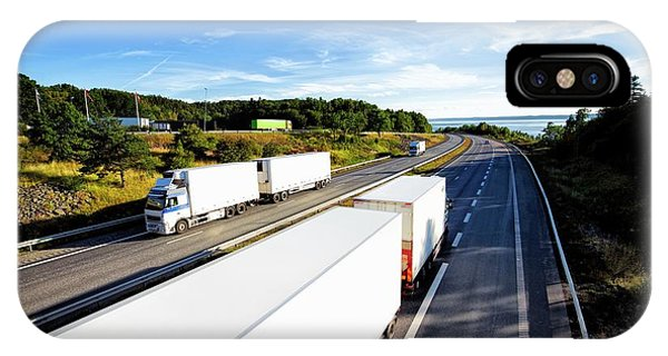 Trucking iPhone Case - Trucks Driving On A Scenic Highway by Christian Lagerek/science Photo Library