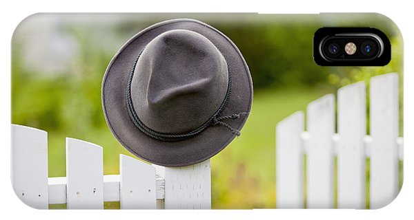 A Hat Hanging On The Post Of A White IPhone Case