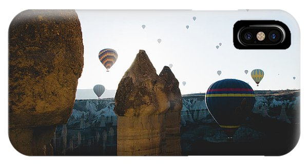 hot air balloons for tourists flying over rock formations at sunrise in the valley of Cappadocia. IPhone Case