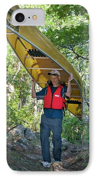 Man Carrying A Canoe IPhone Case by Jim West