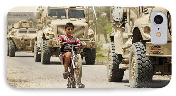 An Iraqi Boy Rides His Bike Past A U.s Phone Case by Stocktrek Images