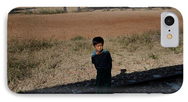 IPhone Case featuring the photograph A Boy In Burma Looks Towards A Train From The Shadows by Jason Rosette