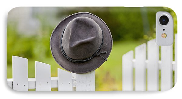 A Hat Hanging On The Post Of A White IPhone Case by Lorna Rande