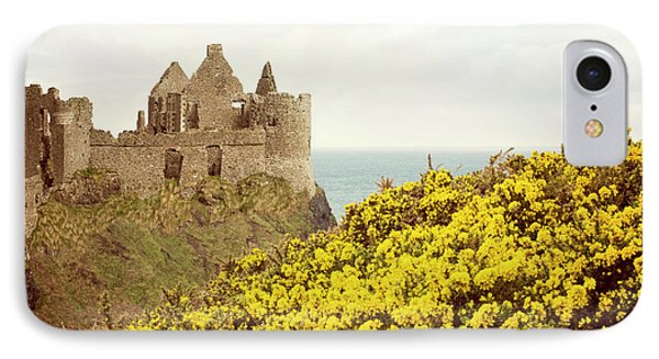IPhone Case featuring the photograph Castle Ruins And Yellow Wildflowers Along The Irish Coast by Juli Scalzi